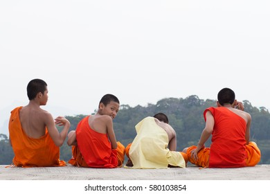 Krabi,Thailand  30 April 2016  :  Four young Thai monk in sat on the floor to talk together, One of them turned his head back in Tiger Temple, Krabi, Thailand