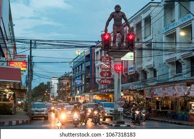 KRABI-TOWN, THAILAND - JANUARY 19, 2017: Motorbikes and cars on the intersection with unusual traffic light decorated with statue of neanderthal which is landmark of Krabi-town in Thailand