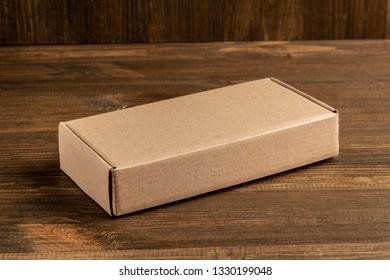 Kraft cardboard box on wooden background, moke up