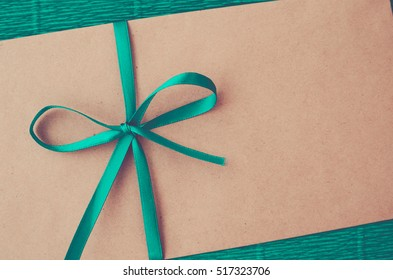Kraft envelope with green ribbon on a green background close-up. Celebratory envelope (vintage)