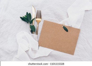 Kraft invitation card with cutlery. Wedding template dinner concept. Top view