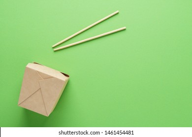Kraft paper or cardboard container and chopsticks on green background. Food delivery concept. Copy space.