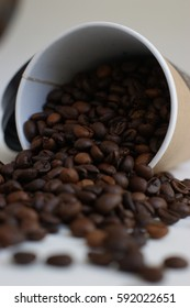 kraft paper coffee cup coffee beans scattered light background