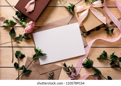 Kraft paper envelope with white card, pink flowers, boxes. Flat lay, top view, wooden table on background. Wedding invitation card. Warm tones.