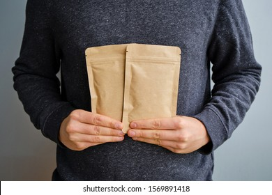 Kraft paper packaging in a mans hands. Packaging for coffee, cosmetics. Packing closeup. Product for sale. Online shopping. Boxes with surprise. Delivery service, shipping. Empty, mockup. Eco friendly