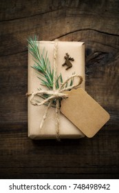 Kraft paper wrapped Christmas gift with a tag tied with rustic jute twine and decorated with green fir branch and wooden reindeer