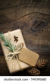 Kraft paper wrapped Christmas gift tied with jute twine with an empty tag and fresh fir branch against rustic wooden background. Overhead view with copy space