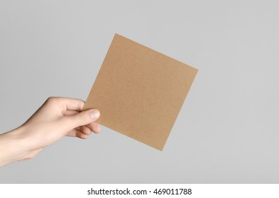 Kraft Square Flyer / Invitation Mock-Up - Male hands holding a kraft flyer on a gray background.