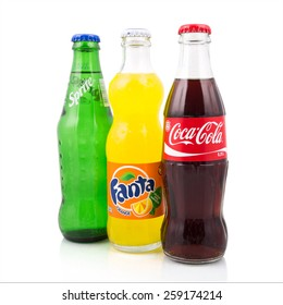 Kragujevac, Serbia  - March 6, 2015: Coca-Cola, Fanta and Sprite glass bottles on white background. These three drinks are most popular brands of Coca-Cola Company based in Atlanta, Georgia.