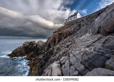 Krakenes lighthouse against a clouded blue sky with the sun breaking through, Vagsoy, Sogn og Fjordane, Norway.
