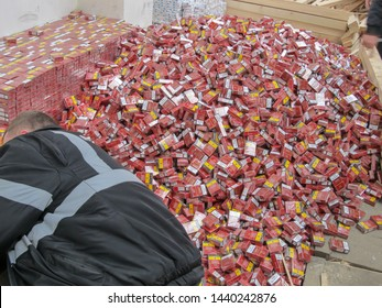 """Krakovets, UKRAINE - MARCH, 2016: The border guarder extracts smuggled cigarettes disguised as industrial wood, checkpoint """"Krakovets-Korchova"""", 70 km west of Lviv. Inscription - State Border Service"""
