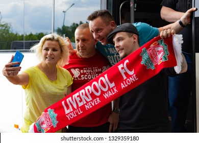 Krakovets, UKRAINE - May 25, 2018: Friendly and happy fans of Liverpool's English football club are photographed with a traveling woman near the bus before the 2018 UEFA Champions League Final in Kiev