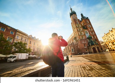 Krakow, Poland - 10 of May 2019: Young man tourist making photo of the famous St. Mary's Basilica on the Market square during the sunrise in Krakow, Poland