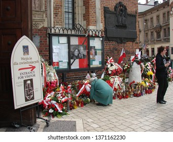 Krakow / Poland - April 15 2010: Flowers and candles in front of entrance to Saint Marys church in Krakow, on wall portrat of tragically died president lech Kaczynski and his wife Maria, people