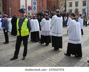 Krakow / Poland - April 18 2010: Priests march in procession during funeral of tragically died President of Poland Lech Kaczynski, secured by policeman and policewoman, city center, cameramans behind