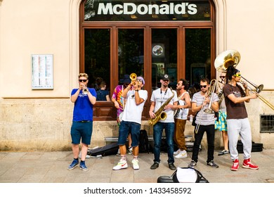 Krakow, Poland - April 26, 2019: street perfomance of group of musicians playing music for people in front of McDonald`s.