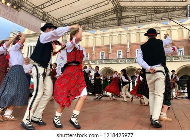 KRAKOW, POLAND - August 10, 2018:  Dancers dressed in traditional folk costumes are dancing on stage during the 42nd International Folk Art Fair in Krakow Main Market Square.