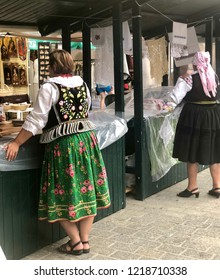 KRAKOW, POLAND - August 10, 2018: Women dressed in traditional Polish outfits sell products at International Folk Art Fair in Krakow, Poland.