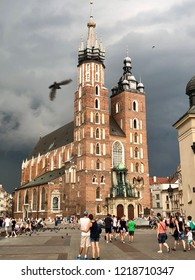 KRAKOW, POLAND - August 10, 2018: Tourists look at St. Mary's gothic church in the Main Market Square of the historic Old Town in Krakow against a cloudy sky.