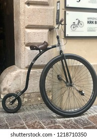 KRAKOW, POLAND - August 10, 2018: A penny-farthing high wheeler bike rests by a wall in historic center of Krakow, Poland.