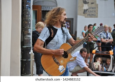 """KRAKOW  / POLAND - AUGUST 16 2010: Tourists watch a busking musician play a 12-string guitar and sings at the Main Market """"Rynek Glowny"""" on the Main Square in Old Town Krakow."""
