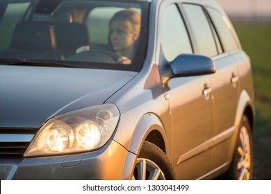 Krakow, Poland - August 25, 2018: Young attractive long-haired woman inside shiny silver car at steering wheel on gravel empty road on bright blurred summer sunny green field and misty sky background.