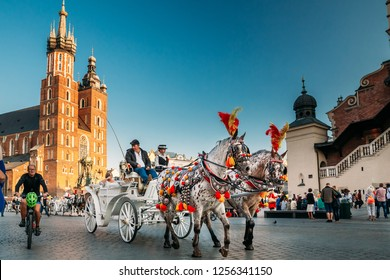 Krakow, Poland - August 27, 2018: Two Horses In Old-fashioned Coach At Old Town Square In Cloudy Summer Day. St. Mary's Basilica Famous Landmark On Background. Church of Our Lady Assumed into Heaven.