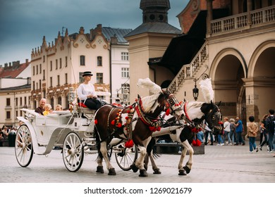 Krakow, Poland - August 28, 2018: Horses In Old-fashioned Coach Carriage Near Cloth Hall Building At Main Market Square In Summer Day. Young Beautiful Woman Working Coachman In Old Town.