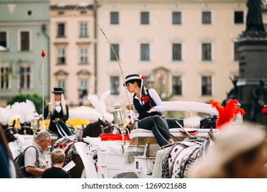 Krakow, Poland - August 28, 2018:  Young Beautiful Woman Working Coachman On Old-fashioned Coach Carriage At Main Market Square In Sunny Summer Day.