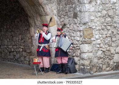 KRAKOW, POLAND - DECEMBER 27, 2017: Street musicians dressed in historical costumes.