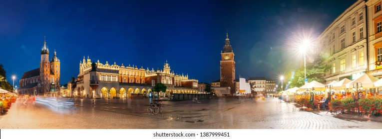 Krakow, Poland. Famous Landmarks On Old Town Square In Summer Evening. St. Mary's Basilica, Cloth Hall Building And Old Town Hall Tower In Night Lighting. UNESCO World Heritage Site. Panoramic View.