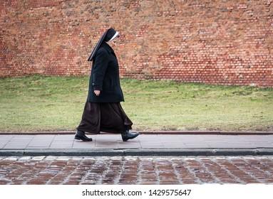 Krakow / Poland - February 13 2016: Nun walking along a street in front of a castle wall in Krakow, Poland.