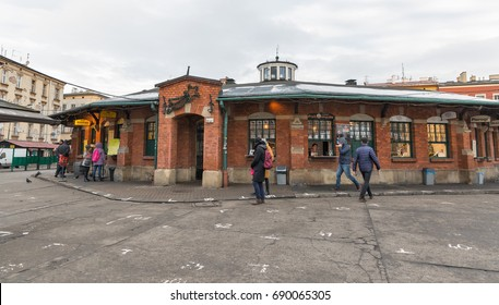 KRAKOW, POLAND - JANUARY 13, 2017: People walk along Plac Nowy or New Square, nice street food place in Kazimierz Jewish quarter. Krakow is the second largest and one of the oldest cities in Poland.