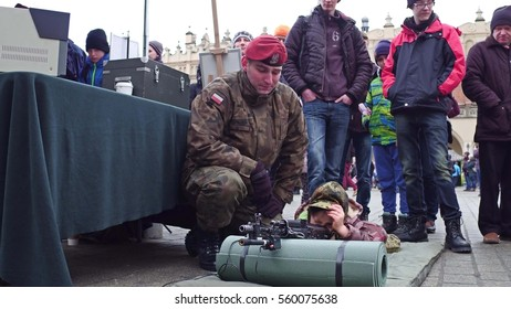 KRAKOW, POLAND - JANUARY, 14, 2017 Polish army officer demonstrates assault rilfe to a little boy. WOSP military show