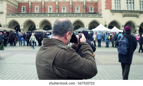 KRAKOW, POLAND - JANUARY, 14, 2017 Mid aged male amateur photographer shooting with Nikon DSLR camera at local town WOSP show