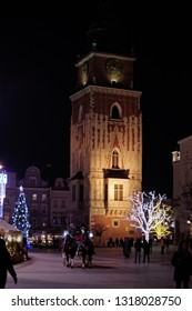 KRAKOW, POLAND -JANUARY 19 2019: People under The Town Hall Clock Tower in the busy historical Kraków's main market square (Rynek)