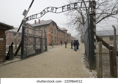 "KRAKOW, POLAND -JANUARY 21 2019: People in front of the entrance of the Auschwitz Nazi concentration camp, Arbeit macht frei is a German phrase meaning ""work sets you free"""