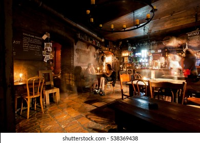 KRAKOW, POLAND - JUL 31: Women talking inside the old style bar with vintage furniture at the dark night on July 31, 2014. Krakow with popul. of 800,000 people has 2.35 mill. foreign tourists annually