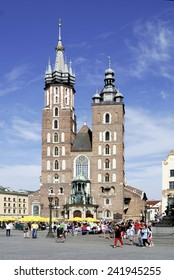 Krakow, Poland - July 13, 2014: People in front of St. Mary's Church on the main market of the old city of Krakow in Poland.
