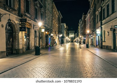 Krakow, Poland - July 17, 2017: Florianska street. A couple of lovers in a calm  deserted street of popular for tourism European city under the light of night lantern, wonderful romantic scene
