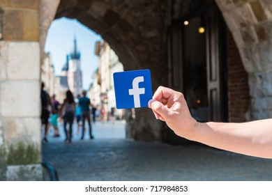 Krakow, Poland - July, 2017:  Logo of Facebook and the city street with lots of people on the background.