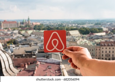 Krakow, Poland - July, 2017: Travel around the world with Airbnb. Logo Airbnb and the city on the background. Home concept. Man holds the logo of a popular company.