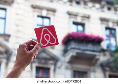 Krakow, Poland. - July, 2017: Travel around the world with Airbnb. Logo Airbnb. Home concept. Big house. Man hand.