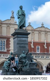 KRAKOW, POLAND - JULY 29, 2010 : The Adamowi Mickiewiczowi Narod (Adam Mickiewicz Monument) in the main market square in the Old Town of Krakow in Poland. It is a bronze monument unveiled in 1898