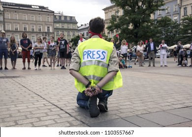 Krakow, Poland, June 01, 2018, man in the press vest and hands tied behind his back protests against censorship and the prohibition of freedom of speech,  people show the government a red card