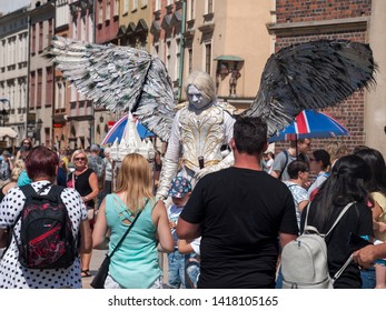 Krakow, Poland - June 03, 2019: Busker / Street performer dressed as an angel with a huge wings, crowd surrounding him waiting to take pictures. Busking, street performing and angel costume concept