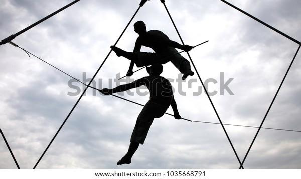 Krakow, Poland - June 06th 2017. Acrobat sculptures hanging on the Bernatek Footbridge.