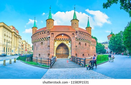 KRAKOW, POLAND - JUNE 11, 2018: The view on Barbakan with preserved part of city moat, surrounded with lush park and edifices of modern neighborhood, on June 11 in Krakow