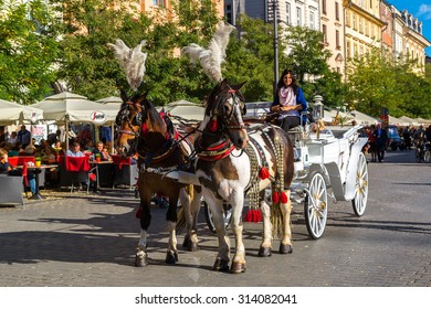 KRAKOW, POLAND - JUNE 16: Horse carriages at main square in Krakow in a summer day, Poland on June 16, 2014