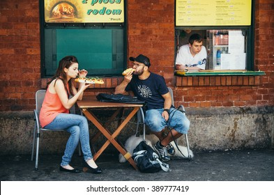 KRAKOW, POLAND - JUNE 26, 2015: The couple eat traditional polish fastfood zapiekanka in Nowy Square.
